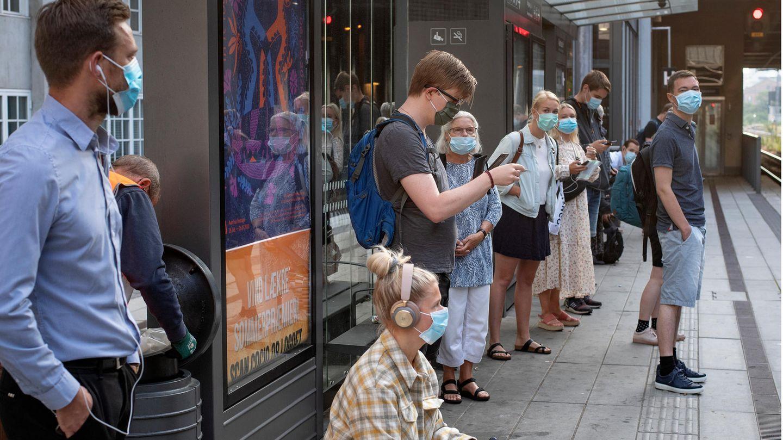Aarhus: Fahrgäste tragen Mundschutze und warten am Bahnsteig auf einen Zug.