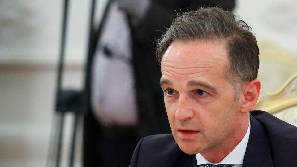 Bundesaußenminister Heiko Maas sitzt im schwarzen Anzug an einem Konferenztisch und spricht in ein Mikrofon