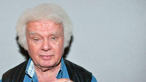 Ein Mann mit weißem Minipli hält eine Zigarre in der linken Hand und schaut gerade in die Kamera