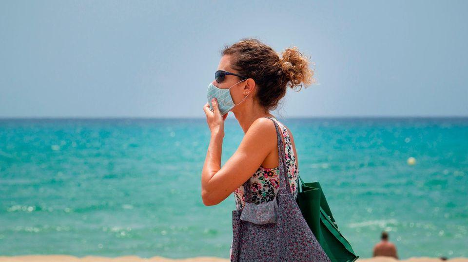 Eine Touristin mit Mund-Nasen-Schutz in Palma de Mallorca