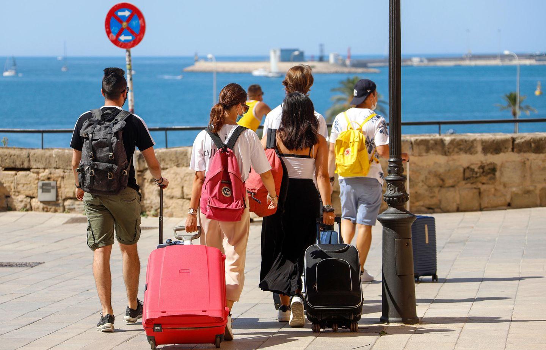 In Sorge vor deutscher Reisewarnung: Touristen ziehen mitRollkoffern durch Palma de Mallorca