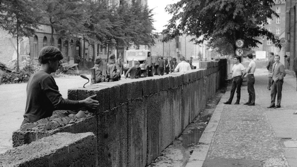 Es traf die Berliner Bevölkerung völlig unvorbereitet: Von der SED-Führung bewusst auf einen frühen Sonntagmorgen gelegt begannen Grenzpolizisten in Berlin heute vor 59 Jahren mit dem Bau der Mauer. Dieses Bild zeigtdie wachsende Sektorengrenze mitten in Berlin fünf Tage später. Mehr als 28 Jahrezementierte die Mauer die Trennung zwischen Ost- und Westdeutschland, bis sie schließlich am 9. November 1989 fiel.In Berlin starben in dieser Zeit nach wissenschaftlichen Erkenntnissen mindestens 140 Menschen durch das DDR-Grenzregime. Insgesamt sollenan der etwa 1400 Kilometer langen deutsch-deutschen Grenze mindestens 327 Menschen ums Leben gekommen sein, die Zahlen sindjedoch umstritten und sollen überprüft werden.