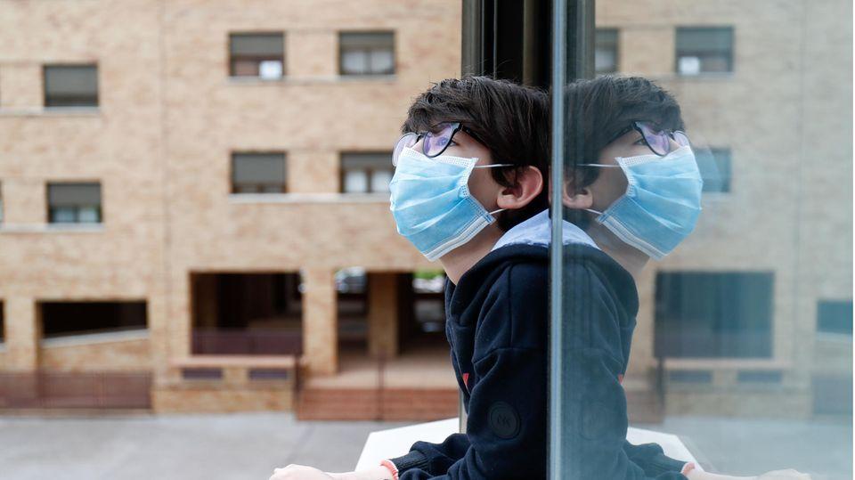 Ein Kind mit Mundschutz schaut aus dem Fenster seines Hauses
