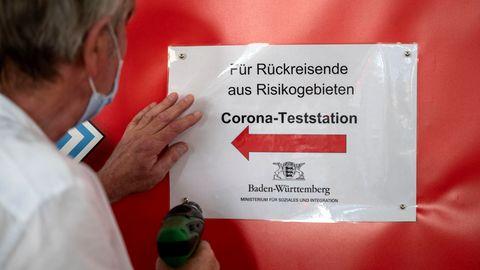 Ein Mitarbeiter des Sozialministeriums bringt im Hauptbahnhof Stuttgart Wegweiser zu einer Covid-19-Teststation für Rückreisende aus Risikogebieten an
