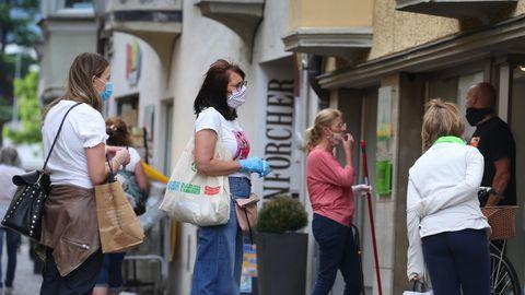 Menschen stehen vor einem Lebensmittelgeschäft Schlange