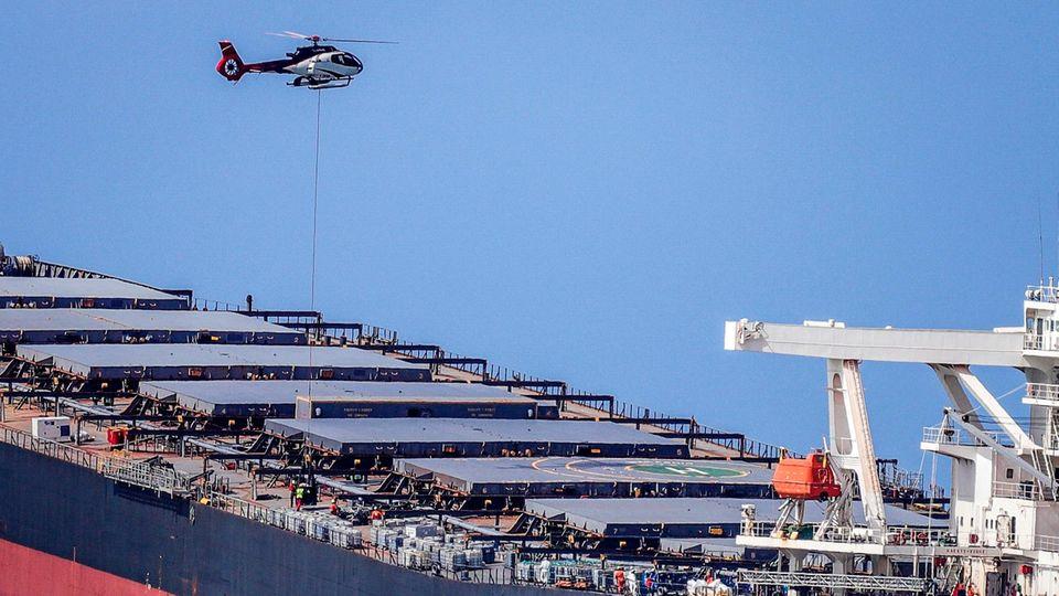 Ein Hubschrauber schweb t über einem riesigen Frachter, der mit dem Heck viel tiefer im Wasser liegt als mit dem Bug