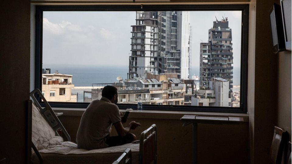 Beirut, Libanon: Vom Aufräumen erschöpft und abgekämpft sitzt ein Mann im Zimmer einesBeiruter Krankenhauses und blickt durch ein zerstörtes Fenster auf die Trümmer seiner Stadt. Mehr als 200 Menschen starben am 5. August bei einer verheerenden Explosion im Hafen der libanesischen Hauptstadt.