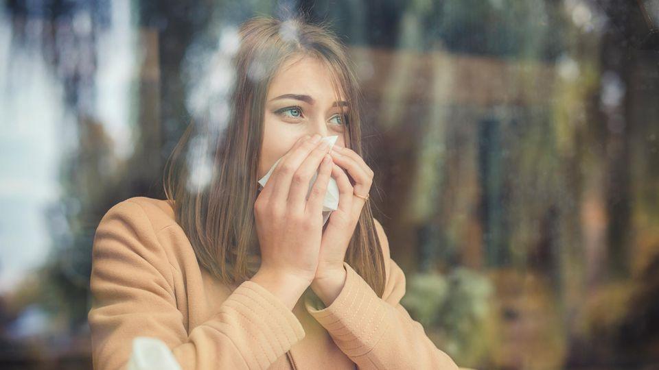 Erkältung Coronavirus: Eine Frau benutzt ein Taschentuch