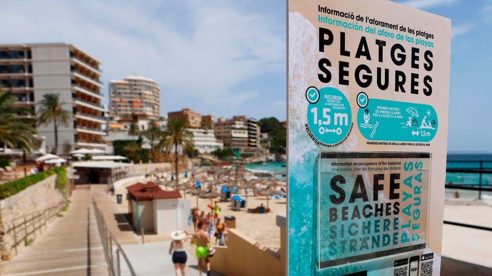 Ein Schild am Weg zu einem Strand auf Mallorca weist auf 1,5 Meter Sicherheitsabstand wegen Corona hin
