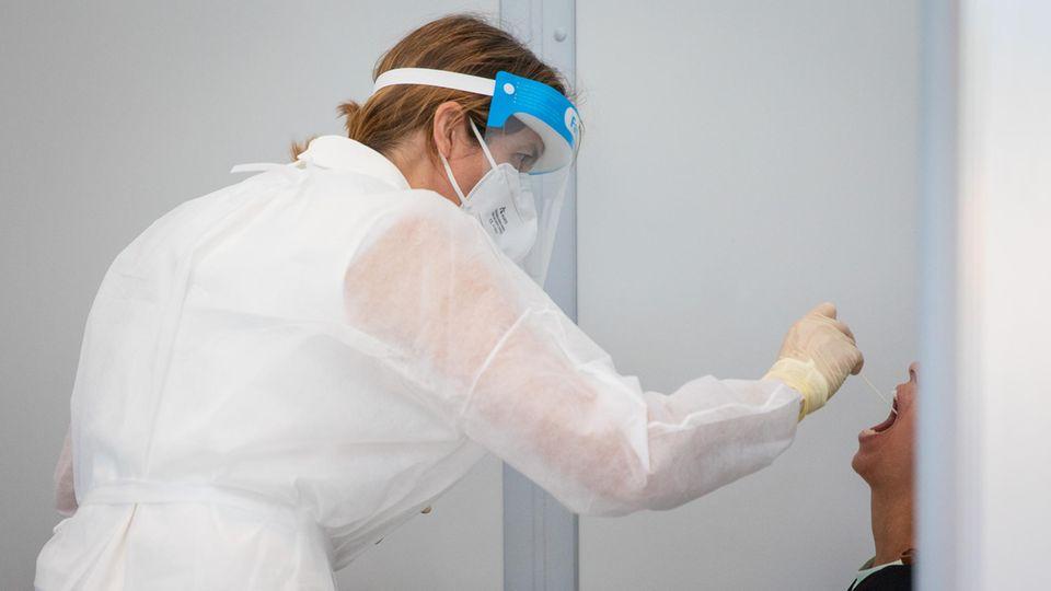 Ein Gesundheitsamtsmitarbeiter macht einen Corona-Abstrich