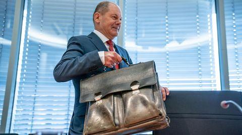 Olaf Scholz trägt eineAktentasche