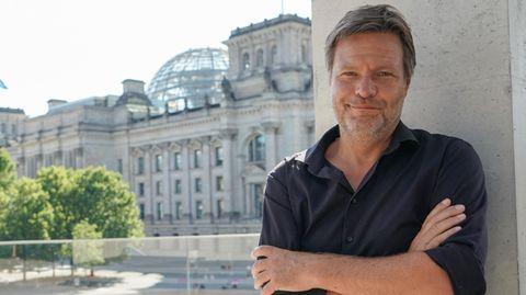 Grünen-Chef Robert Habeck im Sommerhemd, der Reichstag im Hintergrund