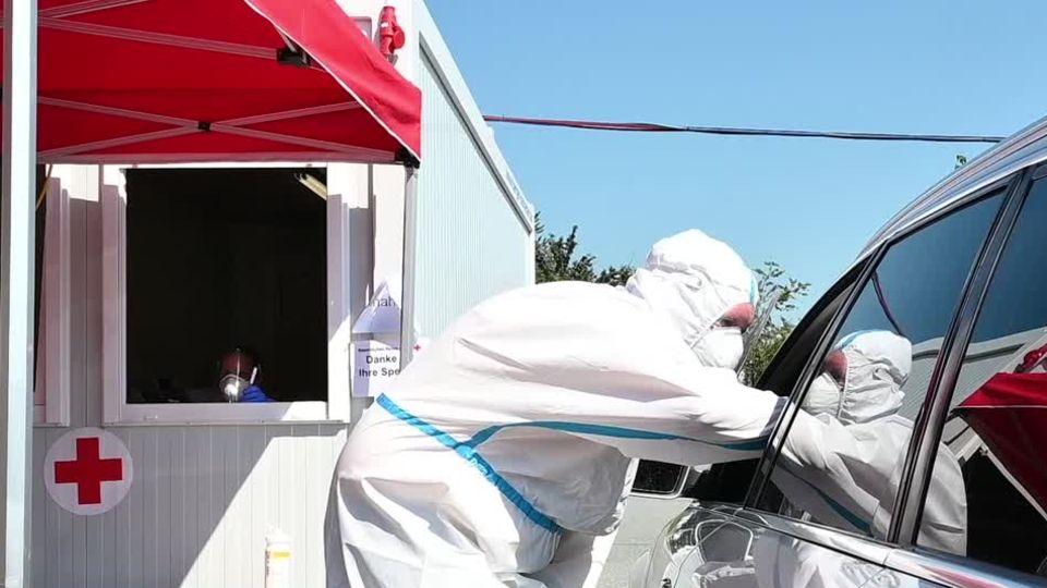 Ein Mann in weißem Schutz-Overall beugt sich an das offene Fahrerfenster eines Autos, um einen Coronatest zu machen
