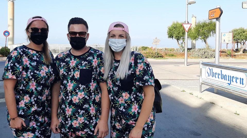 Gerade erstauf der Urlauberinsel angekommen:Sabine (r), Alex und Renate aus Hildesheim stehen mit Maske und im Partner-Look auf Mallorca