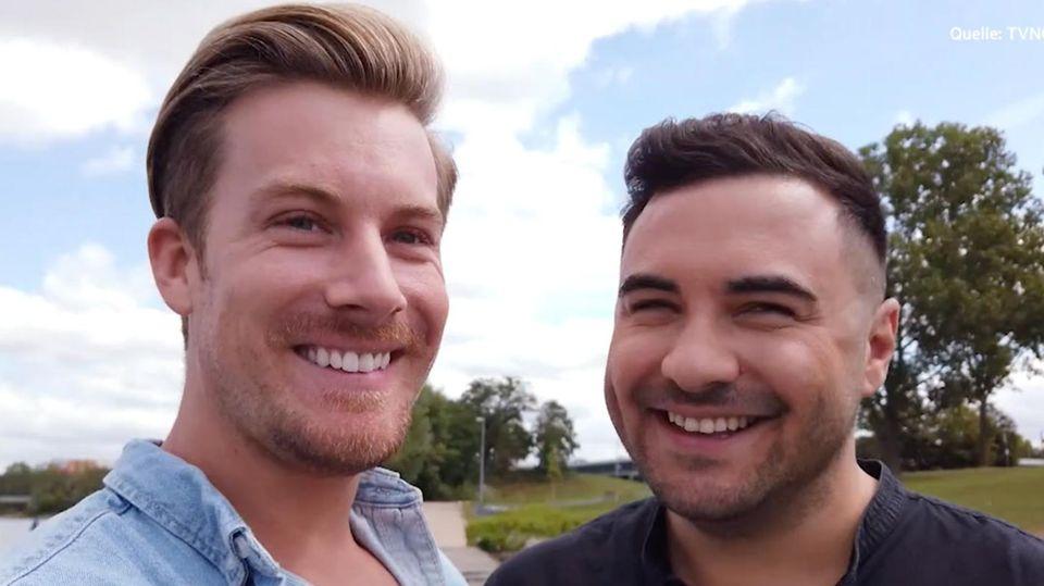 Links lächelt ein größerer blonder Mann in die Kamera, rechts ein etwas kleinerer dunkelhaariger Mann. Beide tragen Scheitel