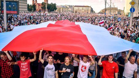 Demonstranten mit der ehemaligen weißrussischen Flagge