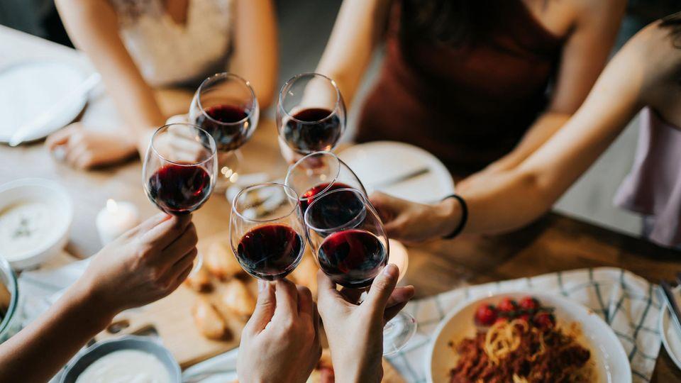 Coronavirus und Innenräume: Freunde stoßen mit Weingläsern an