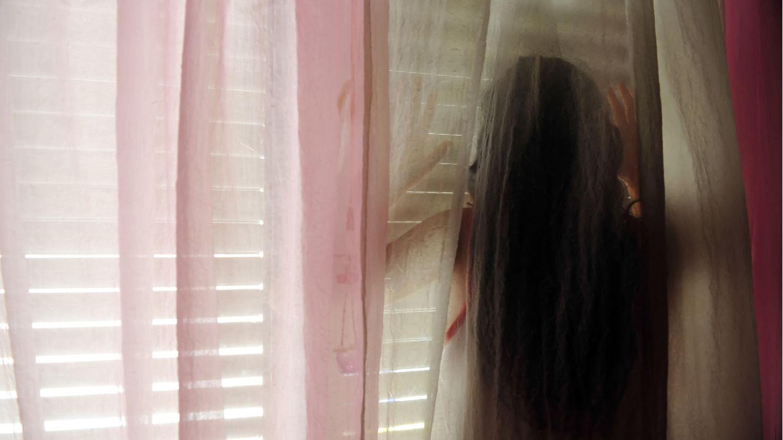 Junges Mädchen steht hinter einer Gardine vor einem Fenster mit einer Jalousie