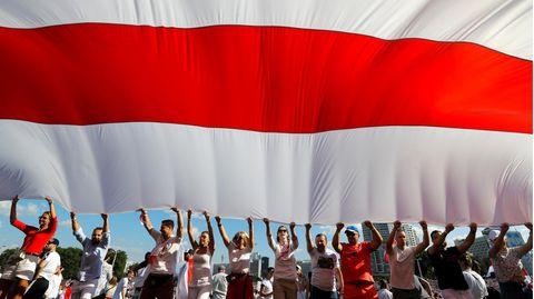 Belarus, Minsk. Anhänger der belarussischen Opposition halten eine riesigeweiß-rot-weiße Flagge