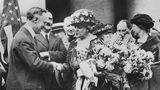 """18. August 1920: Nach langem Kampf -Frauen in den USA erhalten das allgemeine Wahlrecht  Es ist ein historischer Triumph der Frauenrechtsbewegung in den USA: Nach Ratifizierung durch die erforderliche Mindestanzahl von 36 Bundesstaaten tritt am 18. August 1920 das allgemeine Frauenwahlrecht in Kraft. Vorangegangen war ein jahrzehntelanger Kampf der Frauen um politische Teilhabe, zunächst angeführt von der 1863 gegründeten ersten großen Frauenvereinigung des Landes, der Woman's Loyal National League, und später von der in Großbritannien entstandenen Suffragettenbewegung, abgeleitet vom Begriff """"suffrage"""" (Wahlrecht). MitAktionen wie Demonstrationen, Paraden,Hungerstreiks und zivilem Ungehorsam erlangten die Suffragetteneine hohe mediale Aufmerksamkeit.  Vorsitzende der Suffragettenbewegung in den USA war Carrie Chapman Catt. Hier wird sie bei ihrer triumphalen Rückkehr aus Tennessee, dem letzten Staat, der den 19. Zusatzartikel ratifiziert hat, im August 1920 in New York vom mehrmaligen Gouverneur des Bundesstaates,Alfred E. Smith, empfangen. Catt hat ein Bouquet aus blauen und gelben Blumen im Arm, den Farben der National American Woman's Suffrage Association."""
