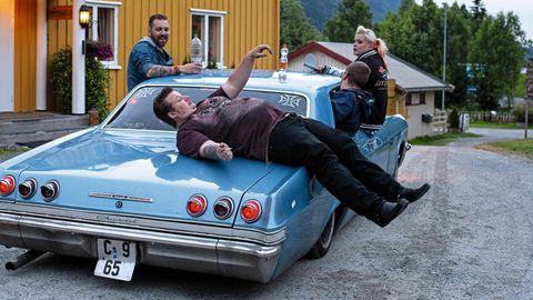 Ein Mann liegt quer auf einem Chevrolet