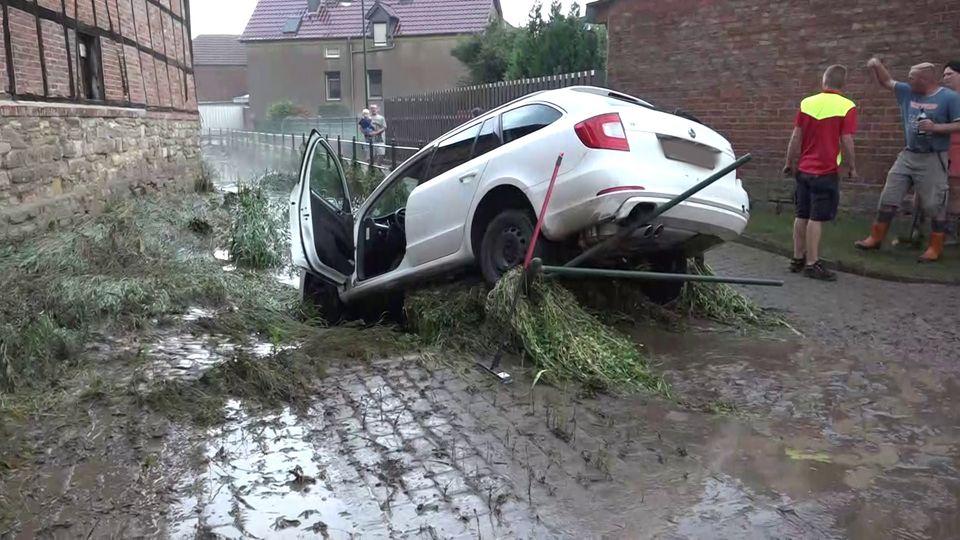 Ein Auto, das von den Wassermassen mitgerissen wurde, hängt in einem Bachbett.