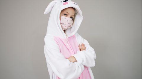 Person in Karnevalskostüm und mit Mundschutz
