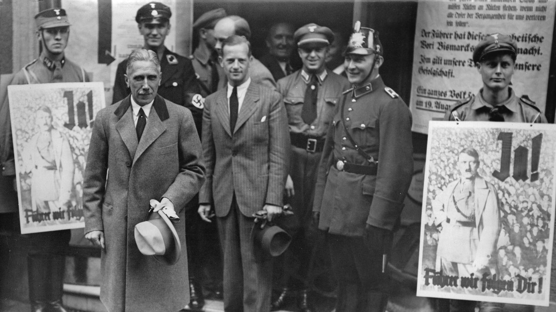 """19. August 1934: Hitler lässt seine Machtfülle bestätigen  Mit einer inszenierten Volksabstimmung lässt Adolf Hitlerdie Zusammenlegung der Ämter des Reichskanzlers und des Reichspräsidenten auf seine Person bestätigen. Er ist damit """"Führer und Reichskanzler"""". Konkret bedeutet das, dass er von daan Staatsoberhaupt, Regierungschef, Oberbefehlshaber der Reichswehr und oberster Gerichtsherr war. Hitler und seine NSDAP hattenin knapp eineinhalb Jahren nach der Übernahme der Reichskanzlerschaft das politische System des Landes komplett verändert.  Auf diesem Bild ist der deutsche Vizekanzler Franz von Papen vor einem Wahllokal in Berlin anlässlich der Volksabstimmung zu sehen.  Die Volksabstimmung gab den Wählerinnen und Wählern keine echte Entscheidungsmöglichkeit.89,9 Prozent der Stimmen fielen zugunsten Hitlers aus. Die Zahl der Nein-Stimmen war dennoch ungewöhnlich hoch. Aber mit der Abstimmung wurden Rechtsstaat und Demokratie beseitigt, die Gewaltenteilung aufgehoben. Deutschland war nun endgültig eine Diktatur, mit Hitler an der Spitze.  Quelle:Bundeszentrale für Politische Bildung"""