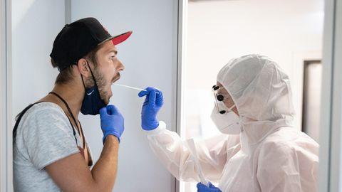 EIne Frau in komplett weißer Schutzkleidung nimmt einem jungen Mann mit heruntergezogenen Mundschutz eine Probe aus dem Mund