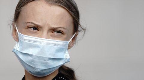 Klimaaktivistin Greta Thunberg trägt einen medizinischen Mundschutz und legt den Kopf schräg