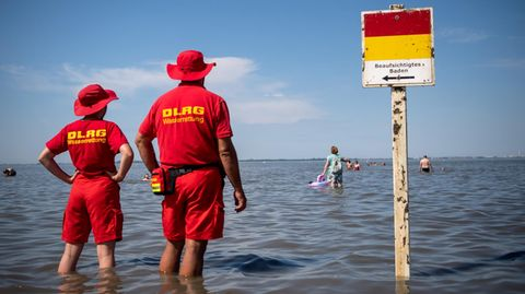 Niedersachsen, Varel: Mitglieder der DLRG (Deutsche-Lebens-Rettungs-Gesellschaft) stehen am Strand von Dangast.
