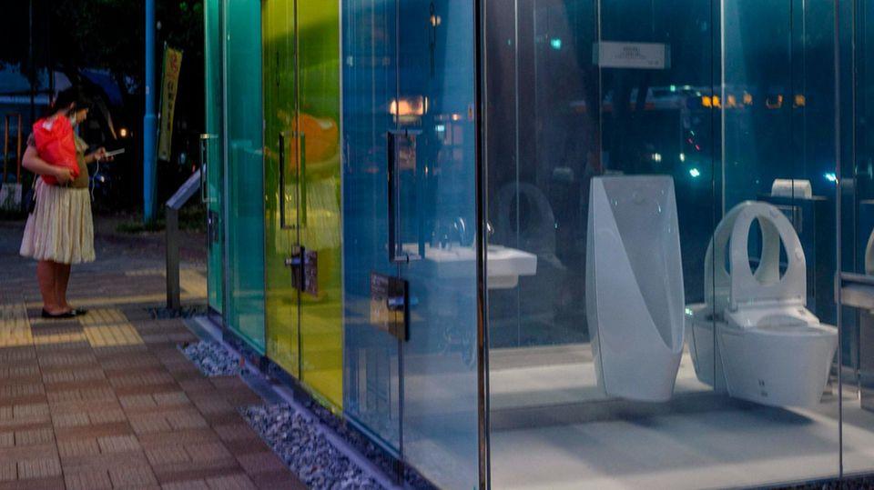 Eine Frau in Rock und rotem Oberteil steht vor einem Toilettenhäuschen, durch dessen Glaswand man eine Toilettenschüssel sieht