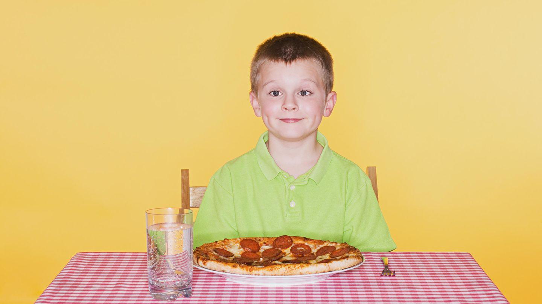 Ein Junge sitzt vor einer Pizza