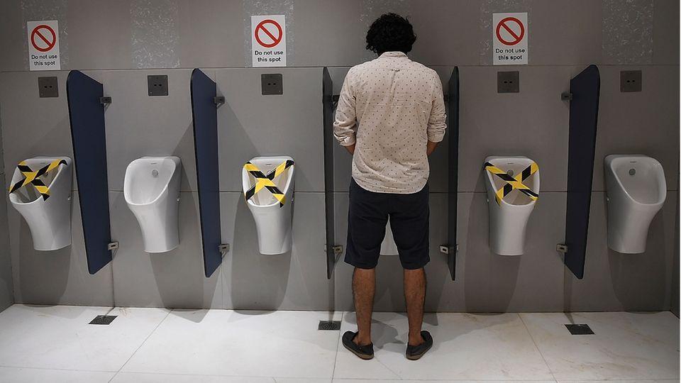 Mann an einem Urinal in Neu Delhi