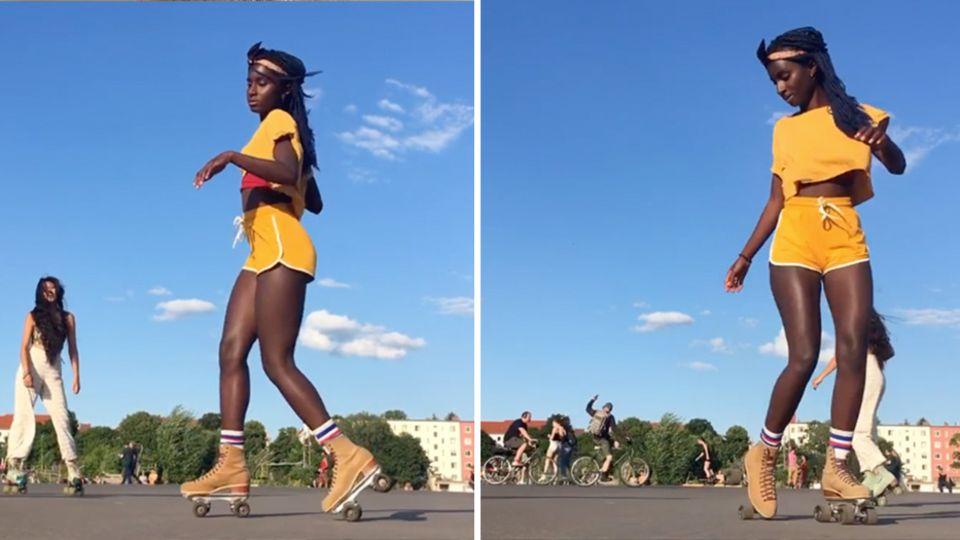 Eine schwarze junge Frau in gelbem T-Shirt und Shorts tanzt auf Rollschuhen