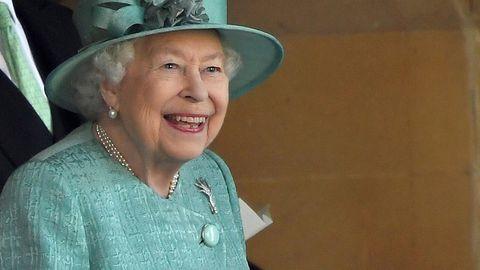 Queen Elizabeth steht in mintgrünem Kostüm und passendem Hut auf einer Tribüne und lächelt breit