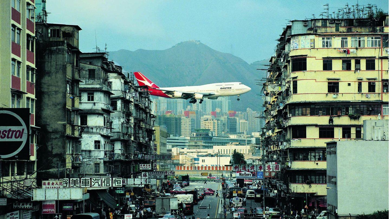 Kai Tak Airport inHongkong  Der 1998 geschlossene Hongkonger Flughafen Kai Tak war definitiv eine Reise wert – für Dietmar Plath mehr als zehnmal. Mitten in der Millionenmetropole gelegen, stellte er eine Herausforderung für die Piloten dar, die über das Häusermeer anfliegen und erst im letzten Augenblick auf die einzige Landebahn einkurven mussten. Fast ohne Vorwarnung erschienen die Jets – hier eine Boeing 747-400 der australischen Qantas – fast zum Greifen nahe über den Köpfen der Spaziergänger in den Straßenschluchten. Ein Spektakel für die Touristen, während die an solche Anblicke längst gewöhnten Einwohner kaum noch den Kopf hoben.