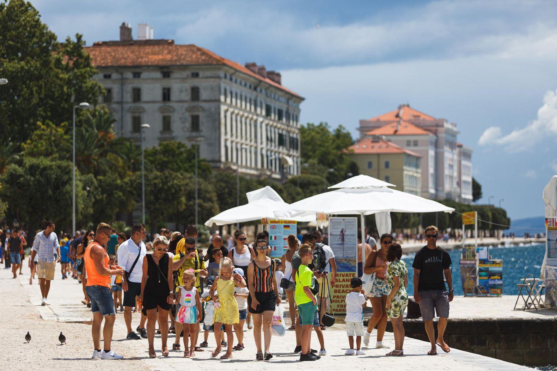 Touristen spazieren an der Uferpromenade von Zadar in Kroatien entlang
