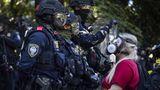 """Portland, USA. Seit Wochen protestieren die Menschenin Portland, Oregon, gegen Polizeigewalt. Auch an diesem Wochenende kam es erneut zu Auseinandersetzungen. Dabei trafenAnhänger der """"Black Lives Matter""""- Bewegung auf antifaschistischeGruppen und rechtsextreme Aktivisten. Diese Demonstrantin trägt zum Schutz vor eingesetztem Tränengas undPfefferspray eine Gasmaske und postiert sich vor den voll ausgerüsteten Polizisten."""