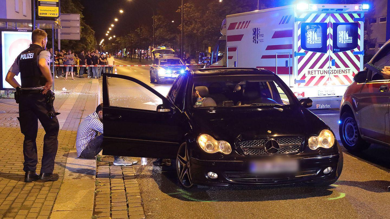Polizisten untersuchen den Unfallwagen