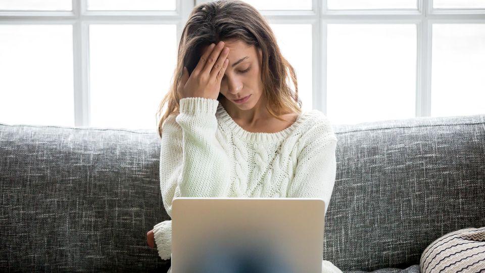 Frau sitzt traurig vor dem Computer