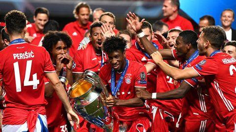 Kingsley Coman (M.) von Bayern München hältdie Champions League-Trophäe und feiert mit seinen Teamkollegen den Sieg gegenParis Saint-Germainim Estadio da Luz