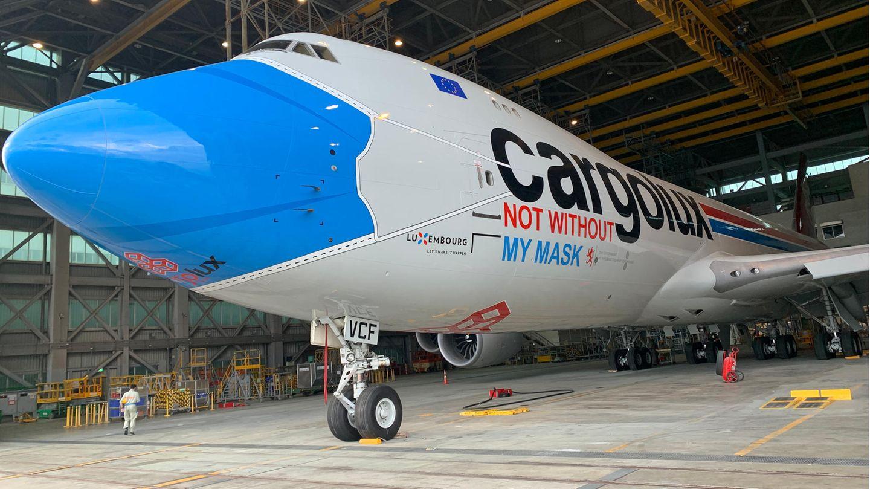 """Die Luxemburger Cargo-Airline hat einen ihrer 30 Frachtjumbos eine blaue Maske verpasst sowie mit dem den Schriftzug """"Not without my mask"""" versehen. Die Boeing 747-8 mit der Kennung LX-VCF transportiert nicht nur medizinische Ausrüstung aus China nach Europa, sondern soll zusätzlich auf das Tragen eines Mund-Nasen-Schutzes hinweisen, um die Ausbreitung der Covid-19-Pandemie einzudämmen."""