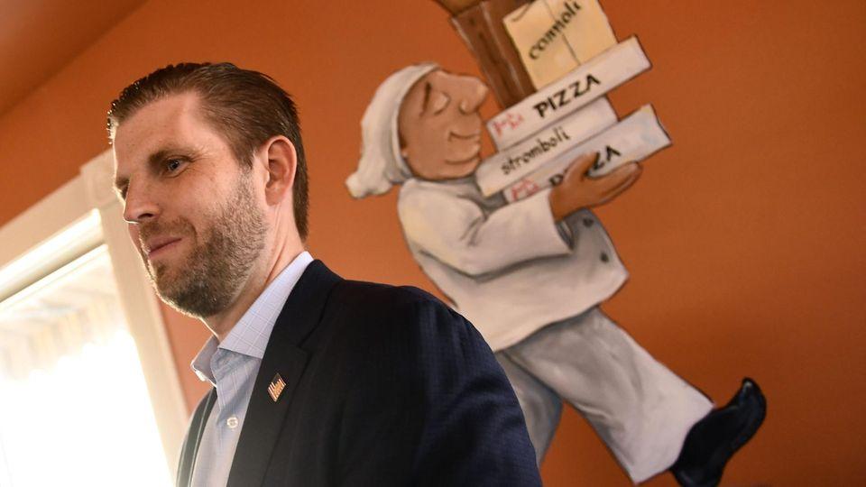 Eric Trump mit dem Bild eines Pizzabäckers an der Wand hinter ihm