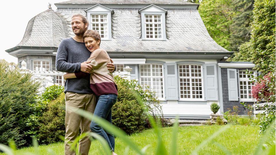Ein Paar vor einem pompösen Haus
