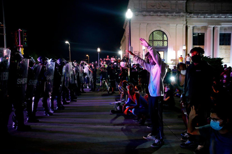Demonstranten stehen teils mit erhobenen Armen einer Reihe Polizisten in voller Kampfmontur gegenüber