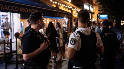 Ein Polizeibeamter und ein Mitarbeiter des Ordnungsamtes stehen vor einem Lokal in Berlin