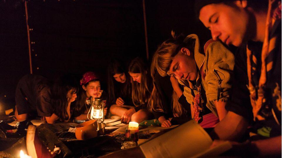 Pfadfinder sitzen um ein Lagerfeuer
