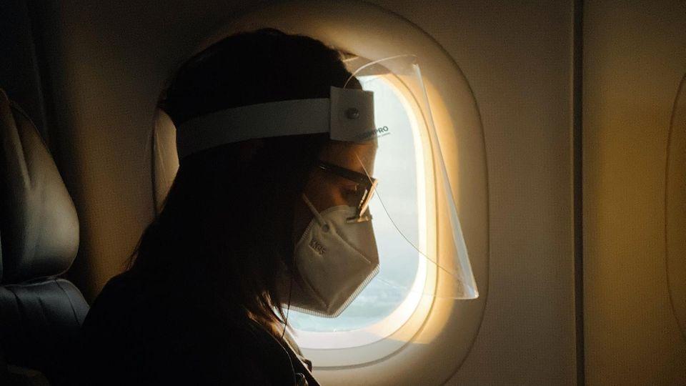 Eine Frau sitzt mit Mund-Nasen-Schutz in einem Flugzeug