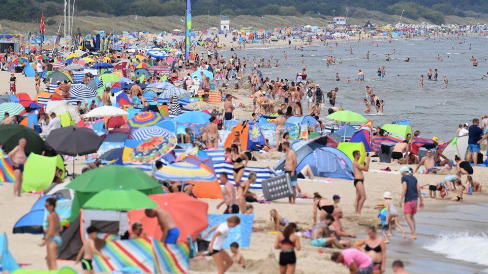 Am Ostseestrand vor der Seebrücke haben sich zahlreiche Badegäste am Strand niedergelassen